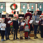 Young singers leading audience in Carol Sing a Long