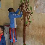 A student decorating a tree with lemurs during a learning activi