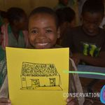 A student showing off a drawing of a house!