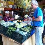 Volunteers Stan and Dennis replenish produce rack