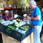 Volunteers Stan and Dennis replenish produce rack