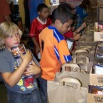 One-Love Soccer Kids help pack bags with food