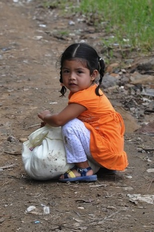 This little girl stopped to rest on her way home from receiving donations. Her new clothes and toys are wrapped up in the cloth.