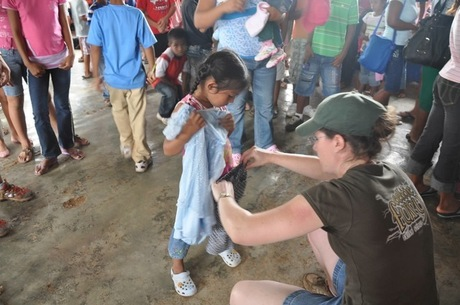 A little girl gets help finding clothes that fit from our founder, Jennifer.