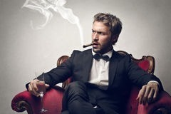 man-smoking-cigar-sittin-armchair-holding-glass-champagne-297965