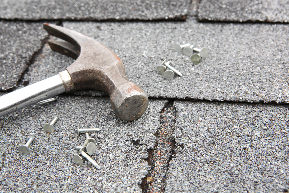 close up of roof shingles and hammer and nails used during a roof replacement