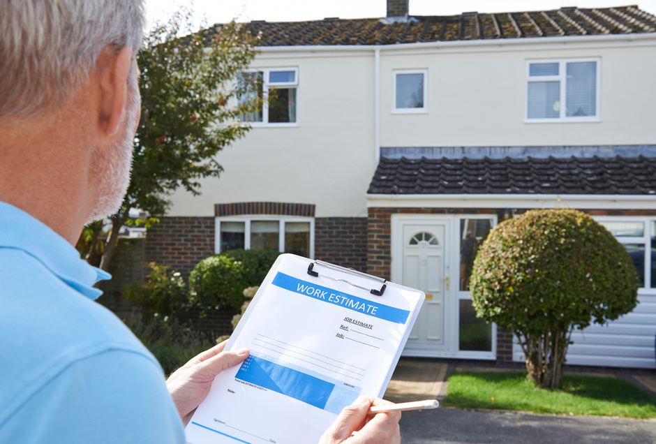 """Man looking at house with """"work estimate"""" sheet in a clipboard in from of him"""