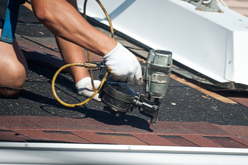 close up of man fixing a roof with a nail gun