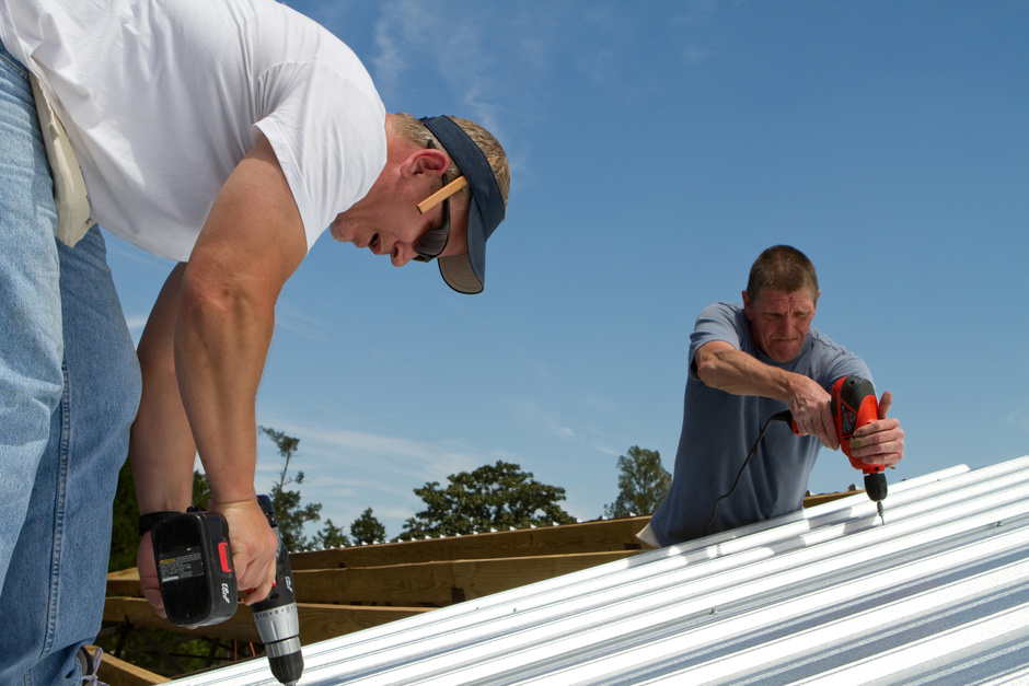 Two men working on sheet metal roofing