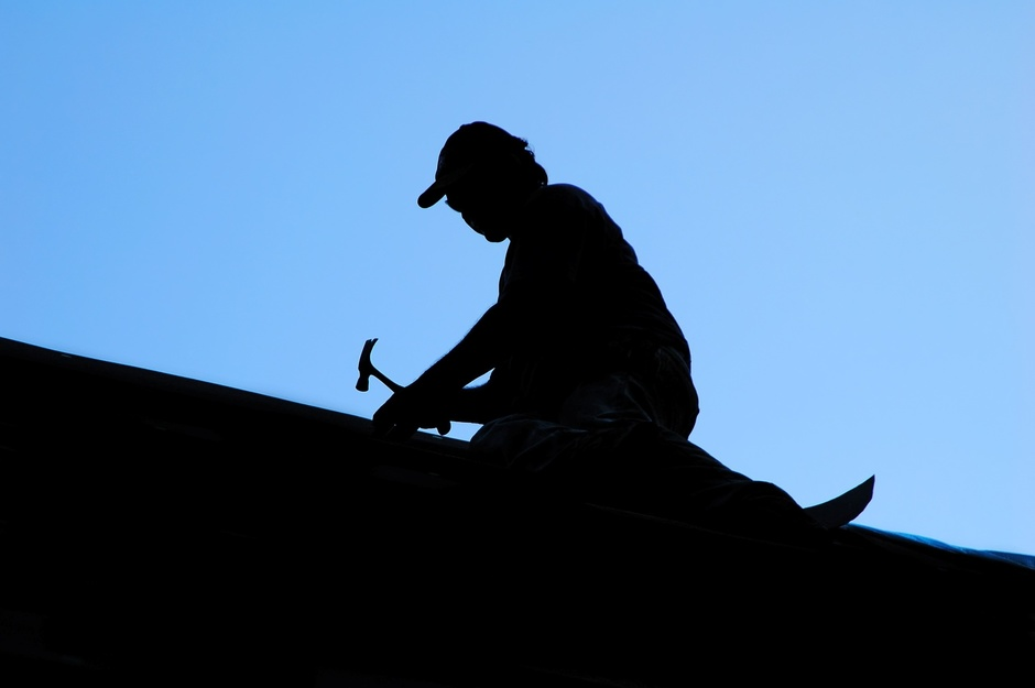 Silhouette of roofer working on a roof.