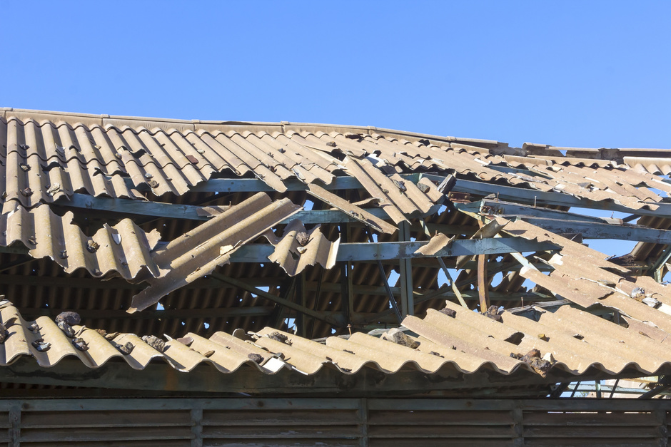 Roof that has been severely damaged by a wind storm.