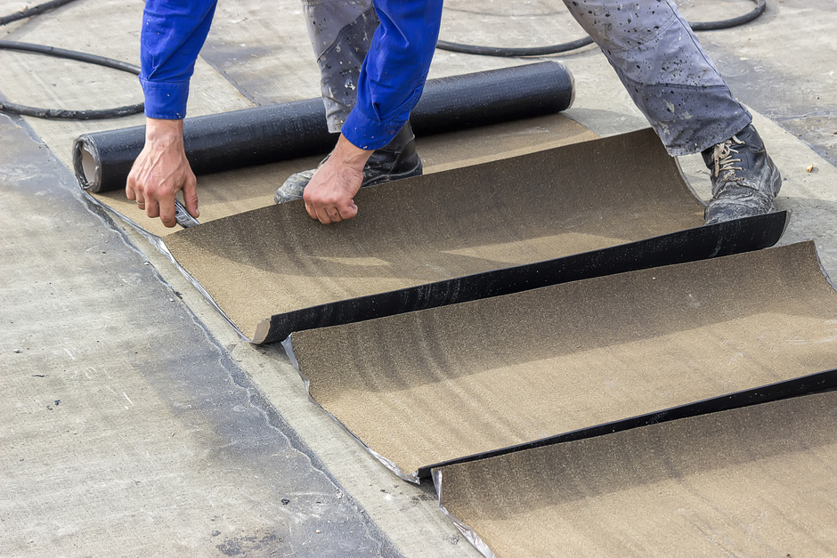 roofing expert unwinding roof coating material atop a home's roof