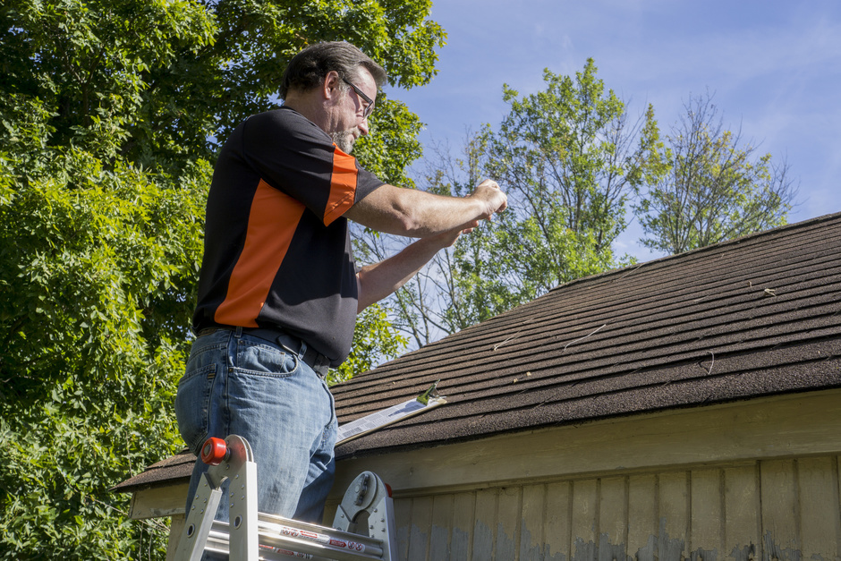 professional roofer fixing a hail damaged roof